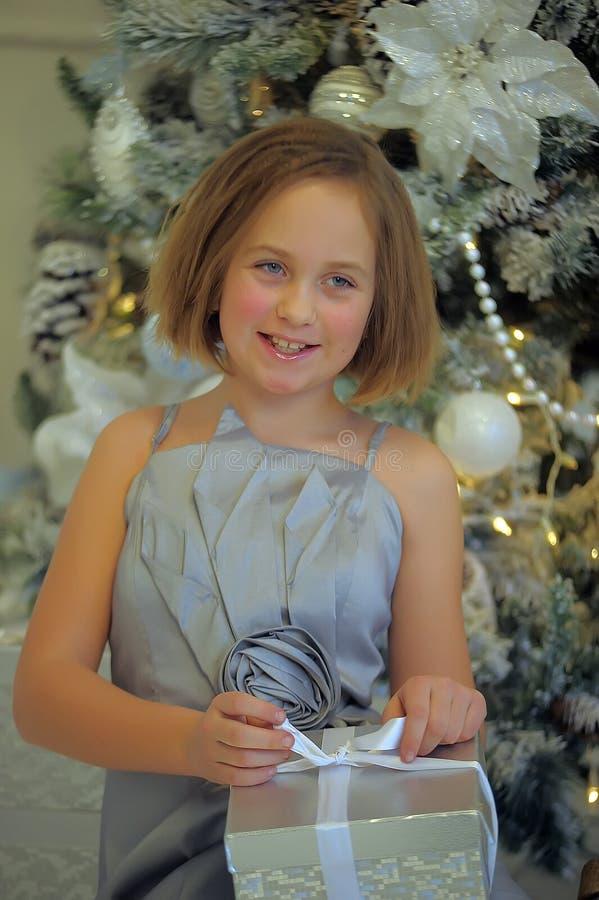Menina em um vestido cinzento pálido com presentes do Natal imagens de stock