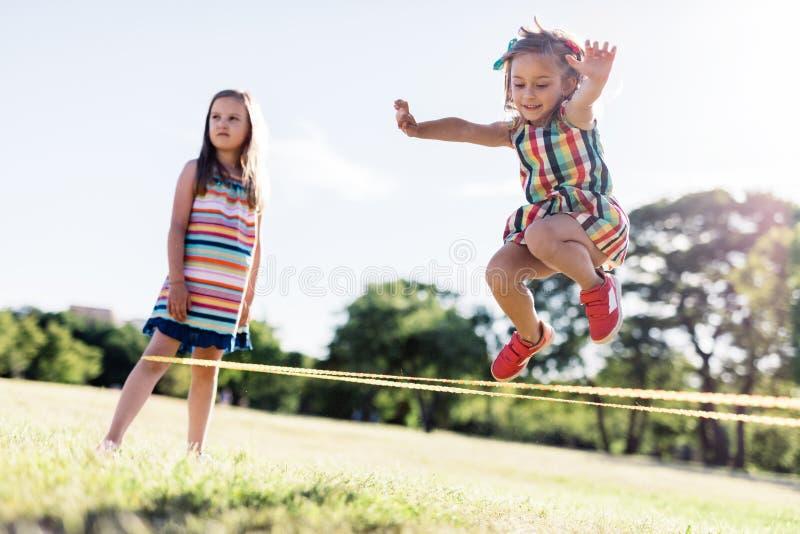 Menina em um vestido colorido que salta através do elástico imagem de stock royalty free