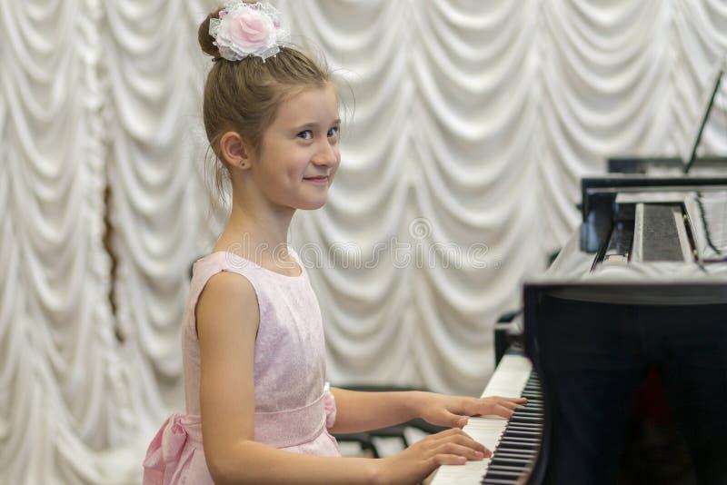 menina em um vestido cor-de-rosa bonito que joga em um piano de cauda preto Menina feliz imagem de stock royalty free