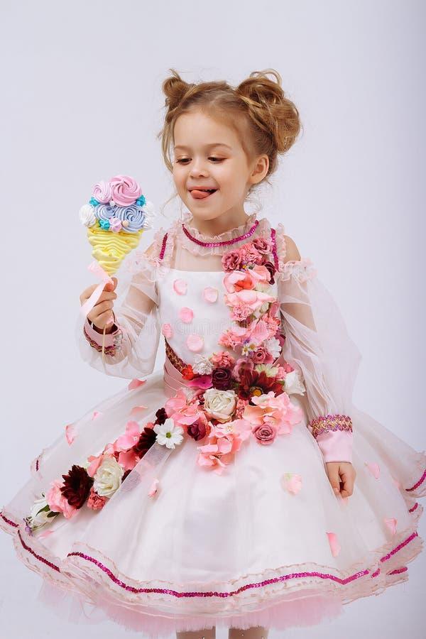 Menina em um vestido cor-de-rosa com as flores que guardam uns doces em uma vara, lambendo, doces na infância Vida doce fotografia de stock royalty free