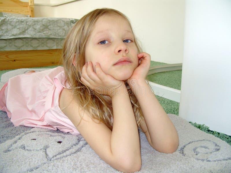 A menina em um vestido cor-de-rosa, olhando em nós. foto de stock royalty free