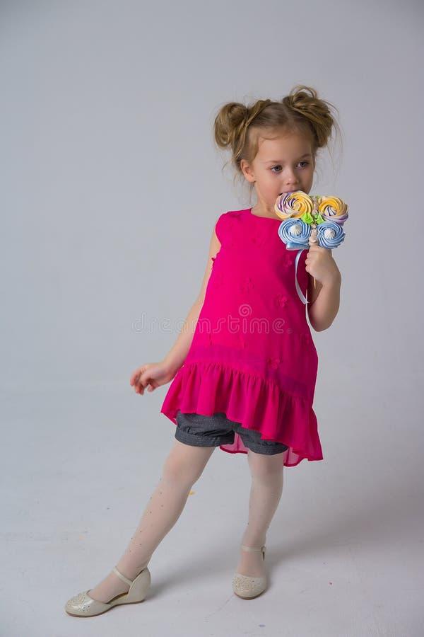 A menina em um vestido coral que guarda uns doces em uma vara, morde-a, doces na infância Vida doce fotos de stock