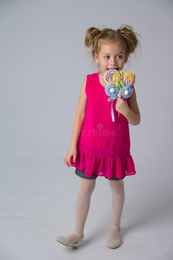 A menina em um vestido coral que guarda uns doces em uma vara, morde-a, doces na infância Vida doce fotos de stock royalty free