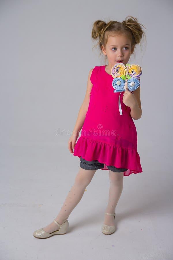 A menina em um vestido coral que guarda uns doces em uma vara, morde-a, doces na infância Vida doce foto de stock royalty free