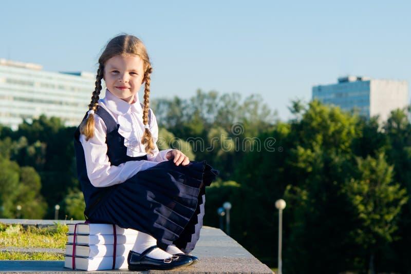 A menina em um vestido da escola, senta-se em uma pilha dos livros de texto fora imagens de stock royalty free