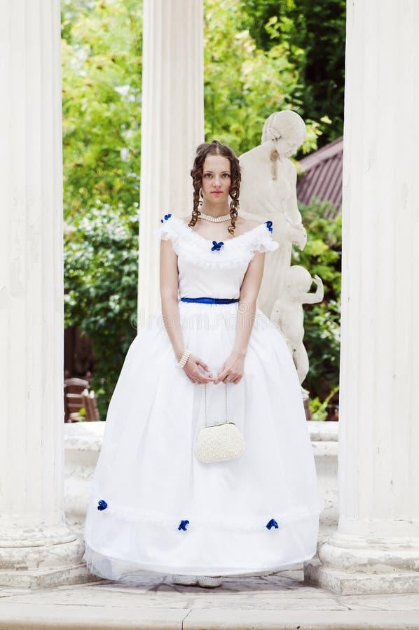 Menina em um vestido de bola na rotunda do verão imagens de stock