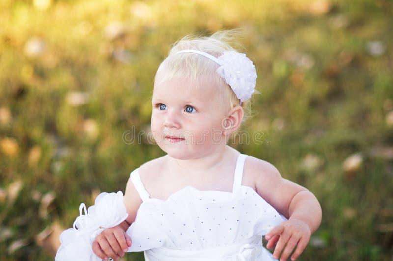 Menina em um vestido de casamento branco na grama fotografia de stock royalty free