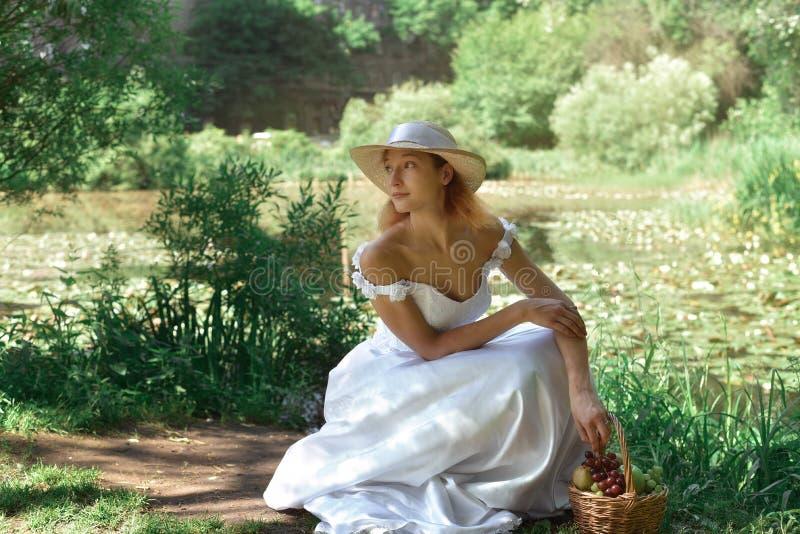 Menina em um vestido de casamento e em um chapéu no parque fotografia de stock royalty free