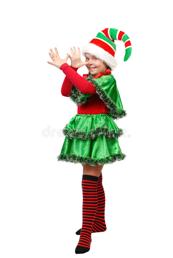 A menina em um vestido do duende do Natal mostra a arrelia imagens de stock royalty free