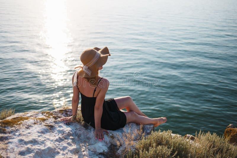 A menina em um vestido e em um chapéu pretos em uma praia rochosa olha o mar imagem de stock royalty free