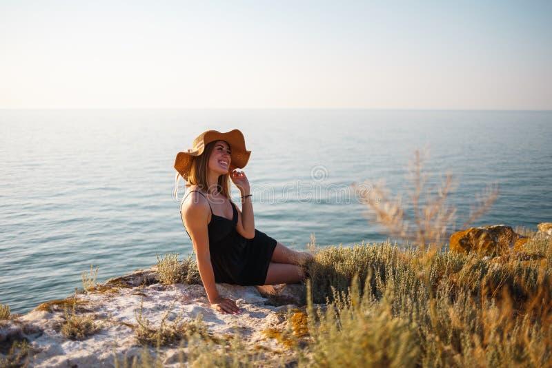A menina em um vestido e em um chapéu pretos em uma praia rochosa olha o mar fotos de stock royalty free