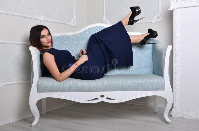 A menina em um vestido encontra-se em um sofá azul fotografia de stock