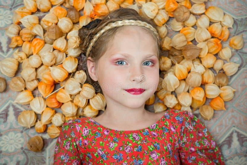a menina em um vestido heterogêneo e em uma trança em sua cabeça descansa nas flores do Physalis fotos de stock royalty free