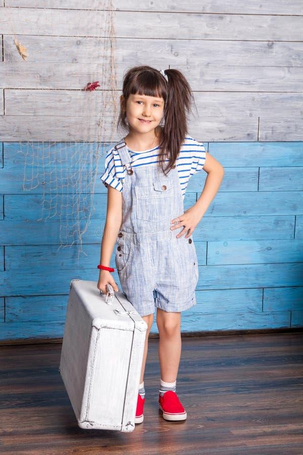 Menina em um vestido listrado que guarda a mala de viagem imagem de stock