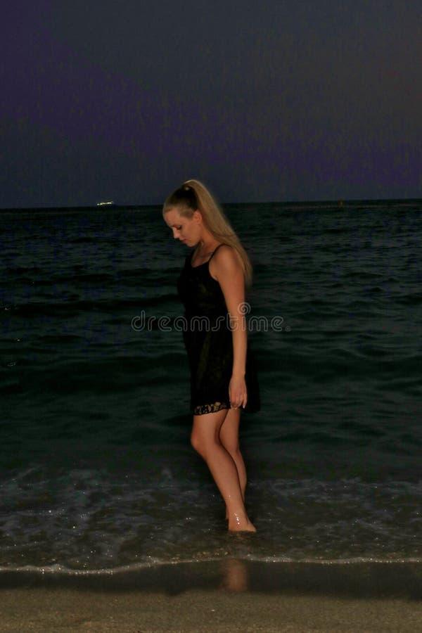 Menina em um vestido preto na costa pelo mar na noite fotos de stock royalty free
