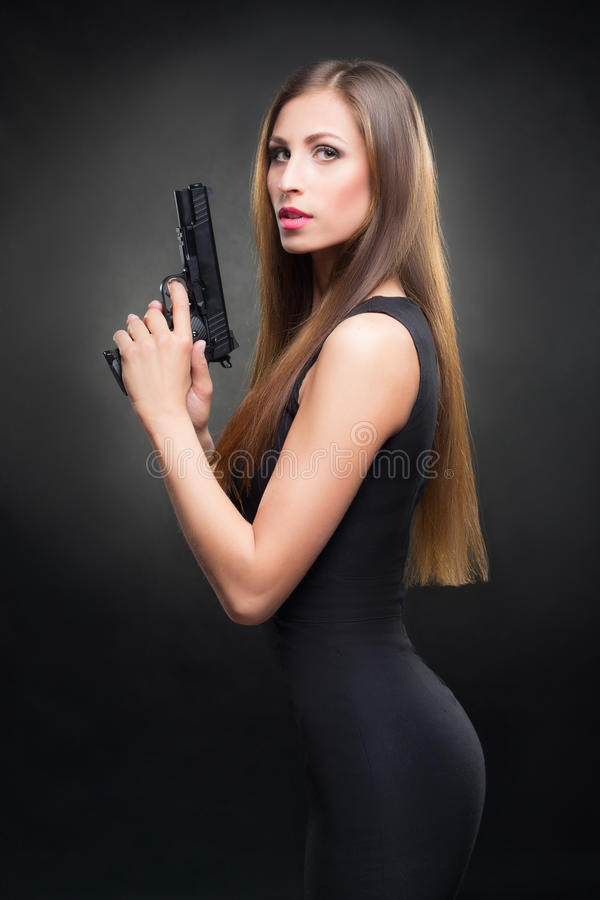 Menina em um vestido preto que guarda uma arma imagem de stock royalty free