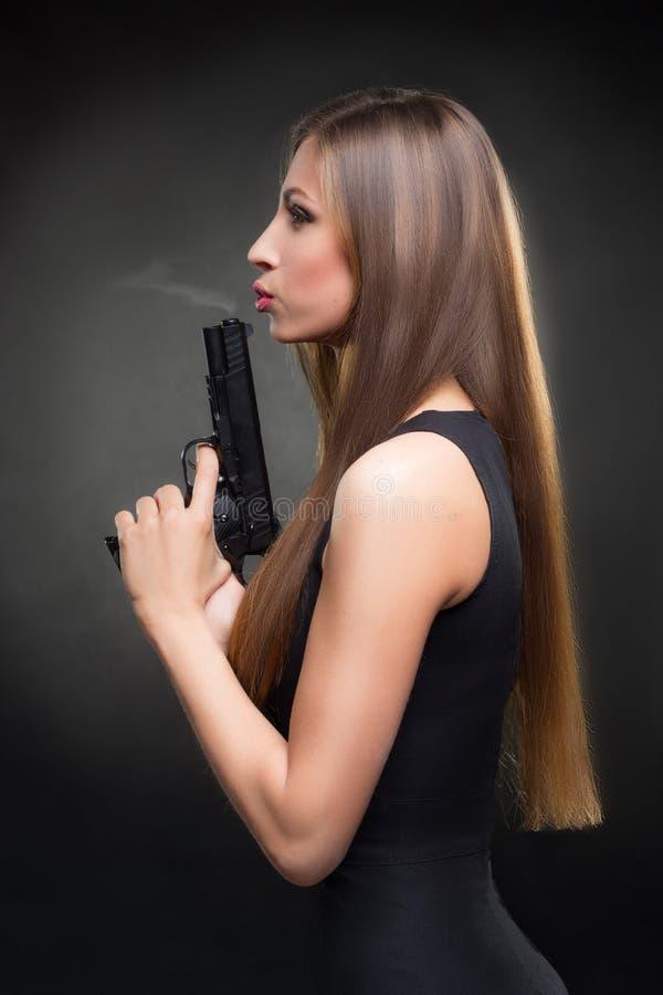 Menina em um vestido preto que guarda uma arma fotos de stock royalty free
