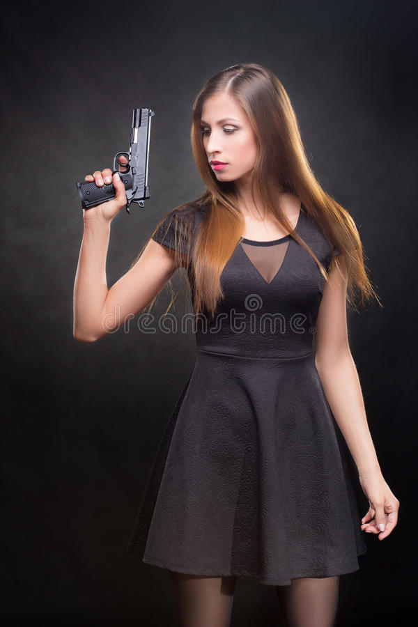 Menina em um vestido preto que guarda uma arma imagens de stock royalty free