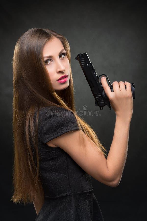 Menina em um vestido preto que guarda uma arma imagem de stock