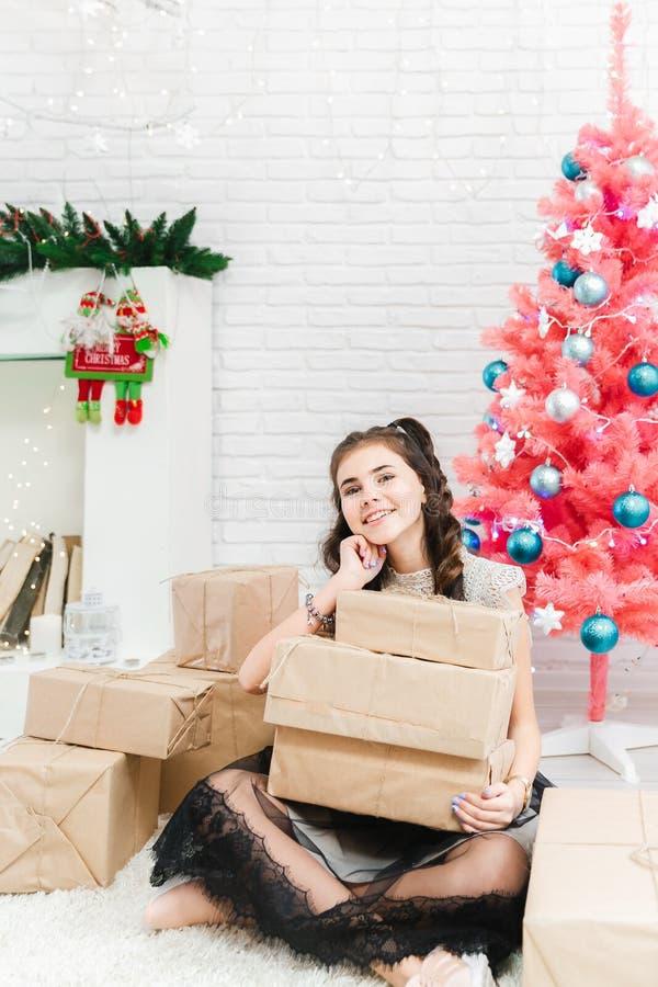 A menina em um vestido senta-se no assoalho em casa perto da árvore cor-de-rosa do Natal e guarda-se caixas com presentes fotografia de stock royalty free
