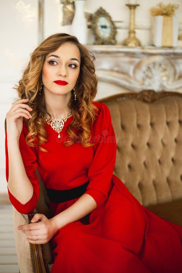 A menina em um vestido vermelho com bijutaria do ouro imagem de stock royalty free