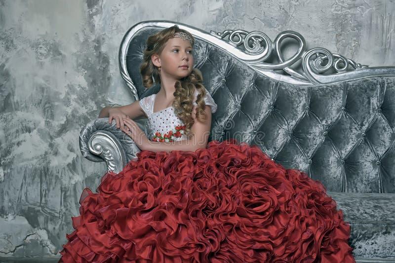 Menina em um vestido vermelho em um sofá imagens de stock royalty free
