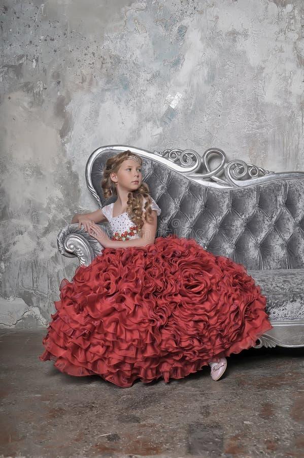 Menina em um vestido vermelho em um sofá imagem de stock royalty free