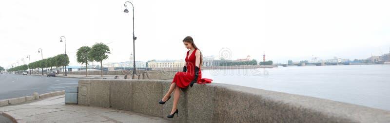 Menina em um vestido vermelho na terraplenagem do palácio em St Petersburg fotografia de stock royalty free
