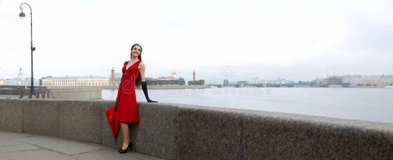 Menina em um vestido vermelho na terraplenagem do palácio em St Petersburg imagens de stock royalty free