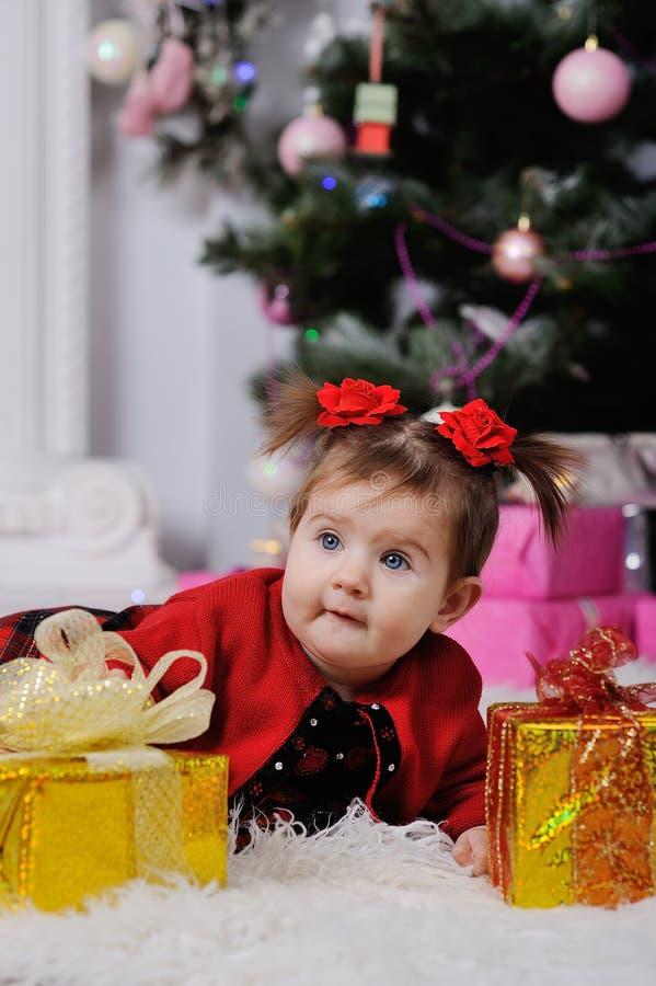 Menina em um vestido vermelho no fundo da árvore de Natal imagens de stock