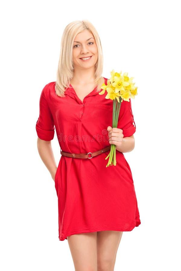 Menina em um vestido vermelho que guarda um grupo das tulipas imagem de stock
