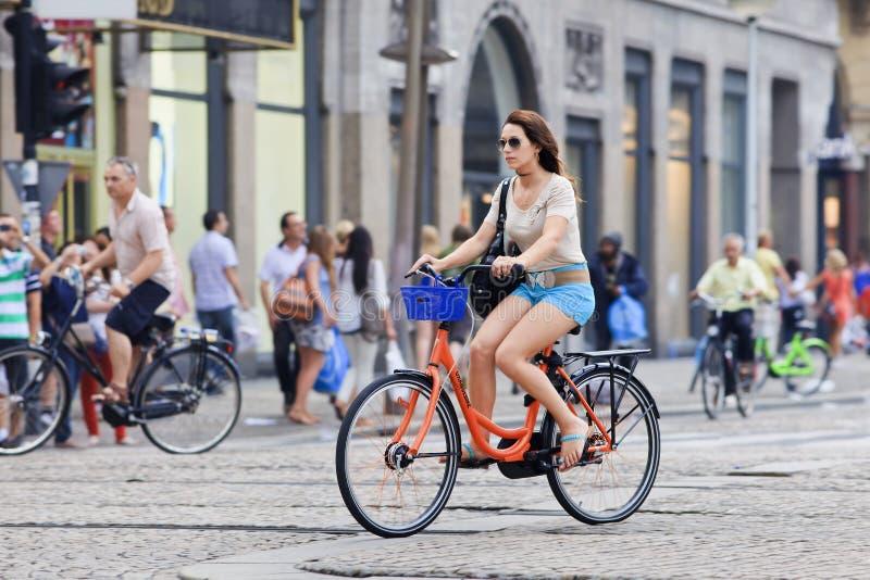 Menina em uma bicicleta alugado perto do quadrado da represa, Amsterdão, Países Baixos imagens de stock royalty free