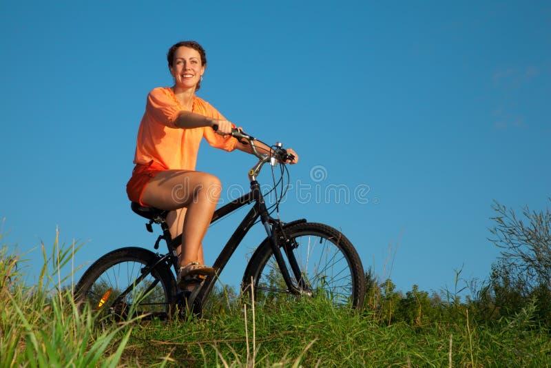 A menina em uma bicicleta na noite do verão fotografia de stock royalty free
