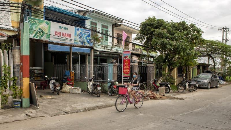 Menina em uma bicicleta que vem para baixo a rua principal da vila de cultivo de Phunong Nam em Vietname imagem de stock royalty free