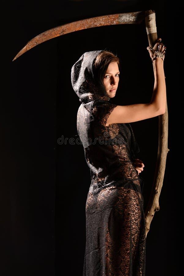 Menina em uma blusa preta do laço com a foice da morte fotografia de stock