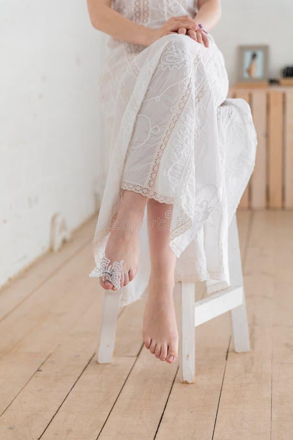 Menina em uma cadeira com uma borboleta artificial fotografia de stock royalty free