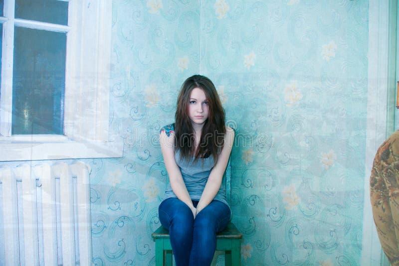 menina em uma cadeira no komnote de canto foto de stock