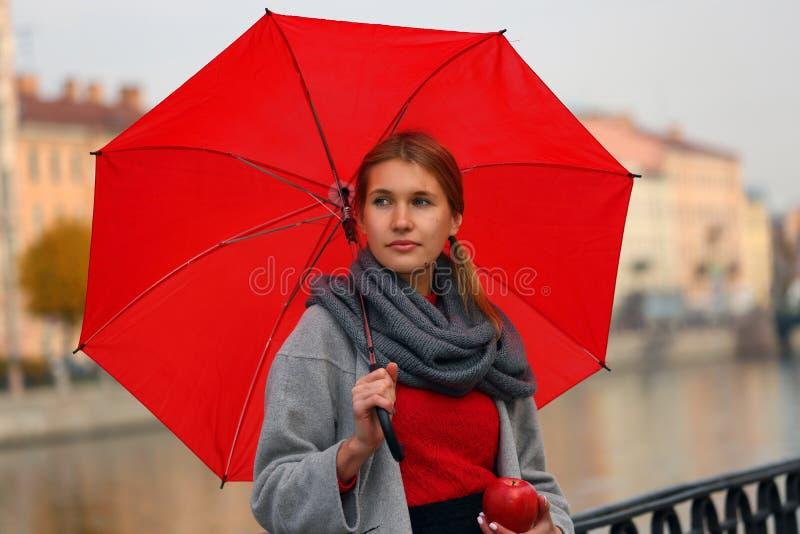 Menina em uma caminhada com um guarda-chuva vermelho e um Apple fotografia de stock royalty free