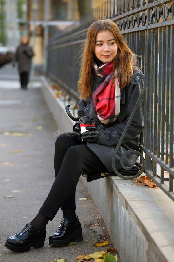 Menina em uma caminhada com uma xícara de café e um guarda-chuva fotografia de stock royalty free