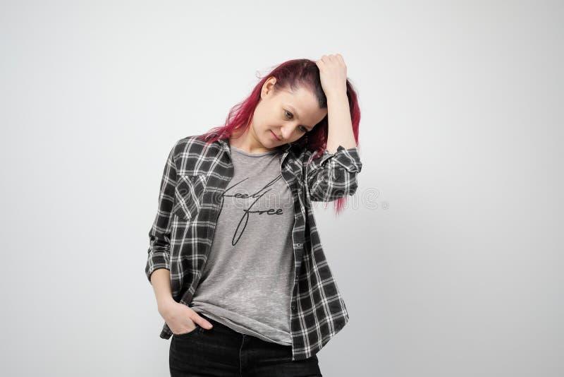 A menina em uma camisa cinzenta da manta em um fundo branco com cabelo vermelho tingido imagem de stock