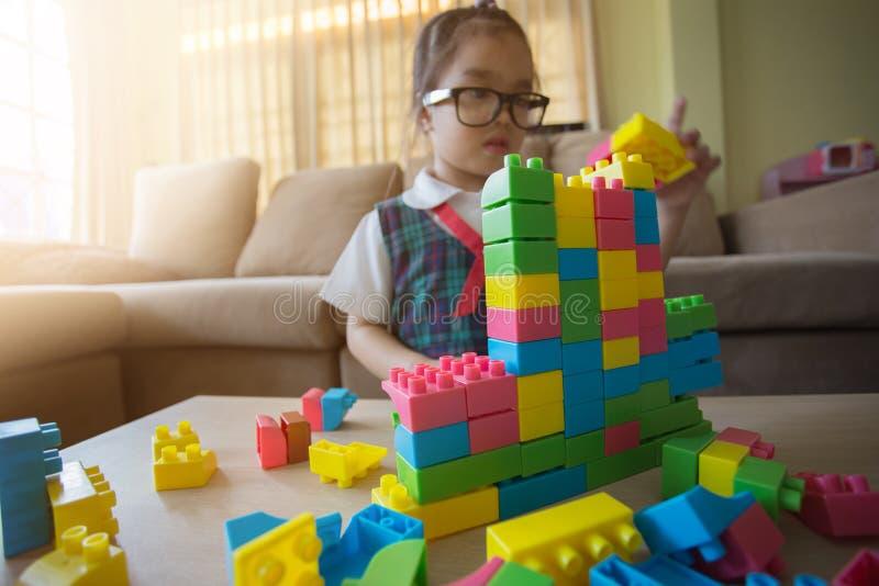 A menina em uma camisa colorida que joga com brinquedo da construção obstrui a construção de uma torre foto de stock