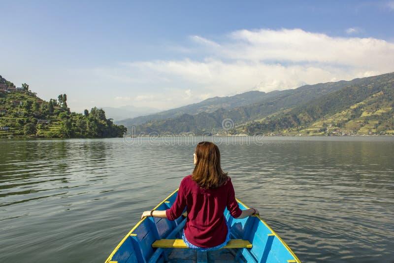 Menina em uma camisa vermelha com cabelo de fluxo em um barco azul de madeira no lago contra o contexto de um vale verde da monta foto de stock royalty free