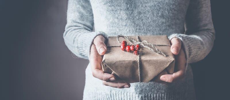 A menina em uma camiseta morna branca do inverno guarda um presente para um ano novo ou um Natal, decorado com um ramo com as bag foto de stock royalty free