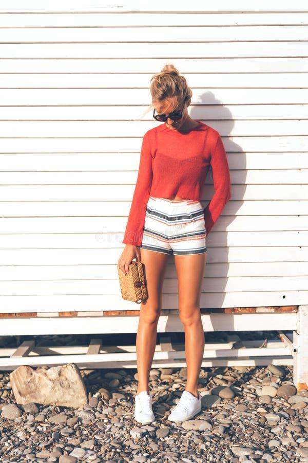 Menina em uma camiseta vermelha e short perto de uma parede branca fotos de stock
