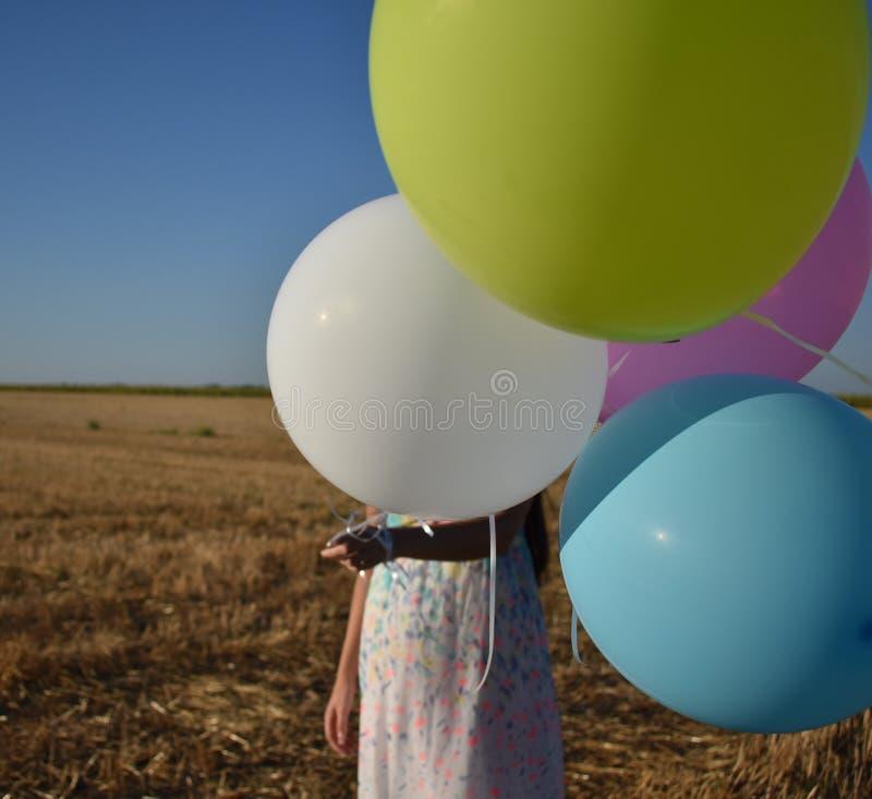 Menina em uma cara escondendo do campo atrás dos balões imagens de stock