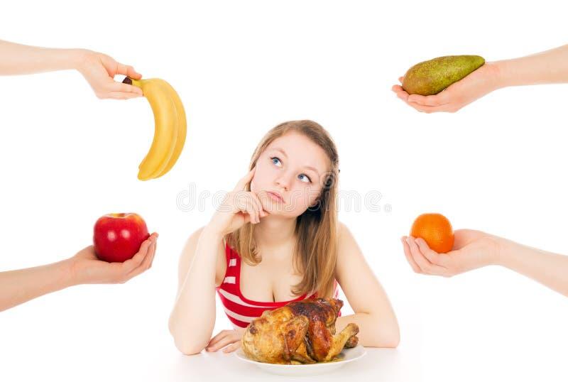 A menina em uma dieta pensa para escolher fotos de stock