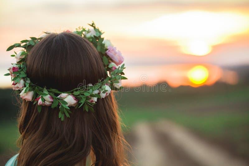 Menina em uma grinalda que aprecia o por do sol no prado fotos de stock royalty free