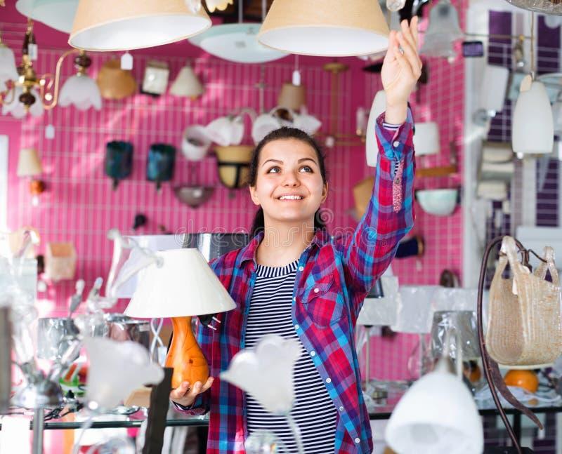 A menina em uma loja mais clara escolhe a lâmpada à moda e moderna do candelabro foto de stock