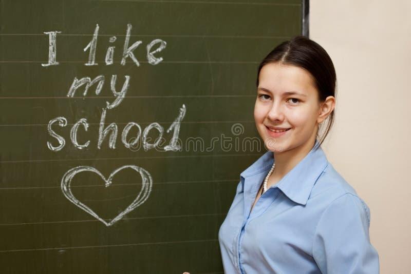 Menina em uma placa de escola imagem de stock