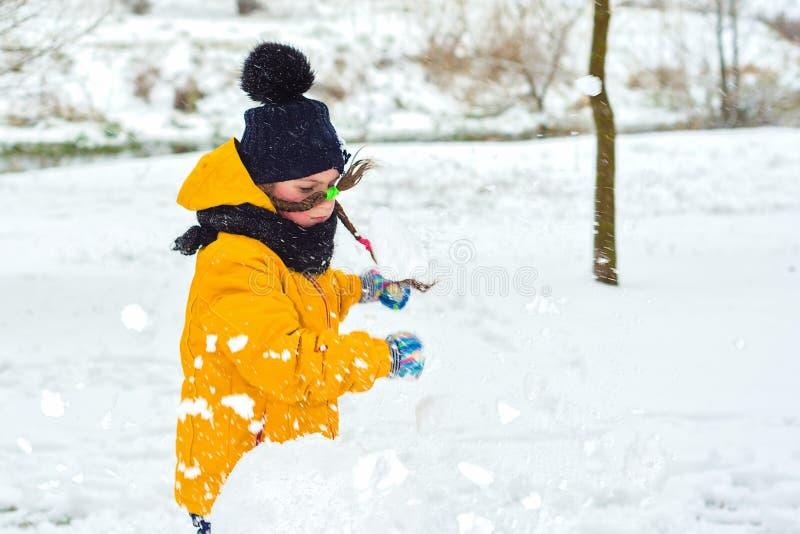 A menina em uma raiva quebrou um boneco de neve fotografia de stock